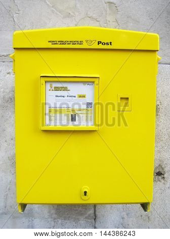 Vienna, Austria - August 14: Yellow mail box on a building wall - Austrian public postal service.