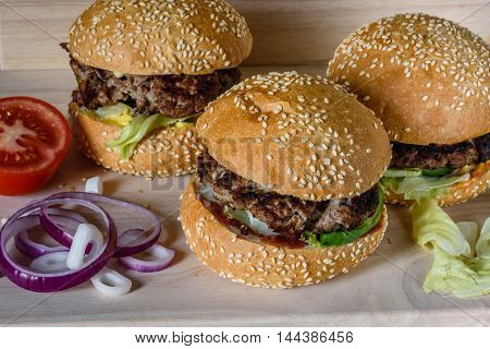 Three fresh burger lay on the board. Homemade fast food more tasty and healthy.