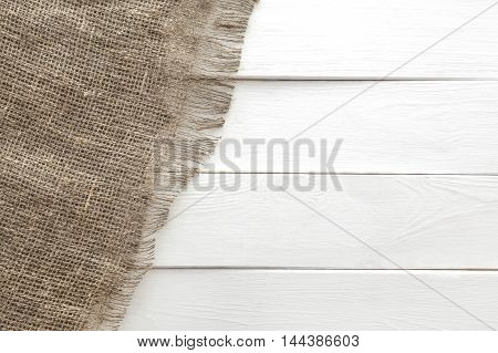 Burlap texture on white wooden table background. Wooden table with sacking