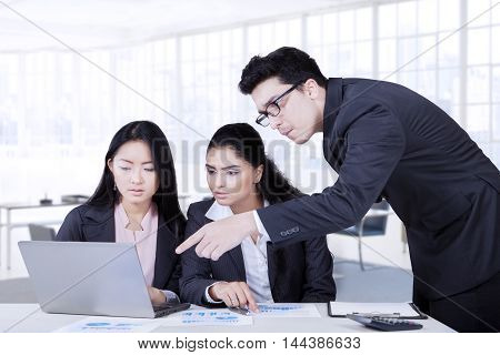 Businessman discussing with his partners while pointing at the laptop in business meeting shot in the office