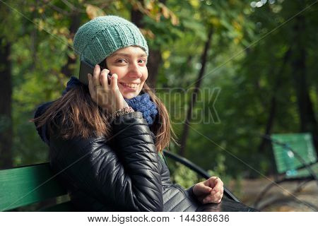 woman in a park talking on the phone