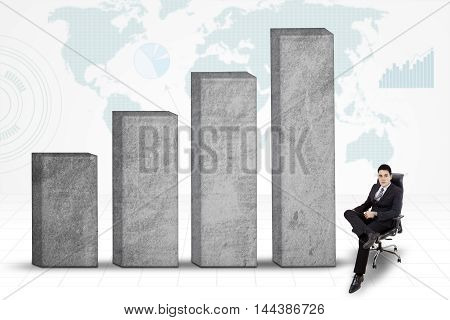 Businessman sits near the growing business graph with world map background