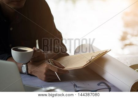 man working on his plane project at site construction work. holding a cup of coffee and pen for check list with vintage effect.