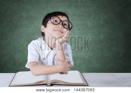 Portrait of a cute female primary school student daydreaming in the classroom while wearing glasses