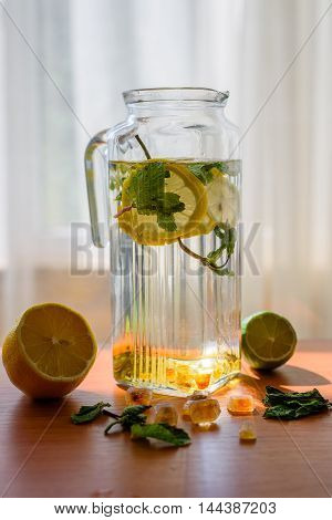 Homemade lemonade with scattered ingredients on window background. Refreshing in the heat. Copyspace.
