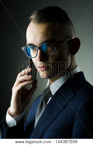 young fashion businessman with nerd glasses and stylish hairdo in jacket speaking on mobile phone posing on grey background