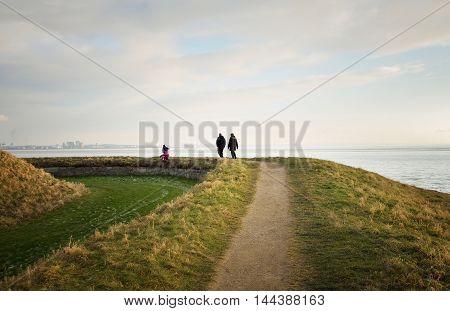 family walks along the shore of the Strait of Oresund
