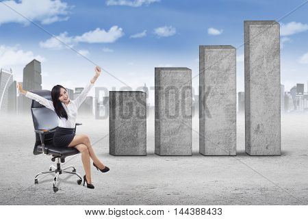 Portrait of successful businesswoman sitting on the office chair while raising hands with financial graph