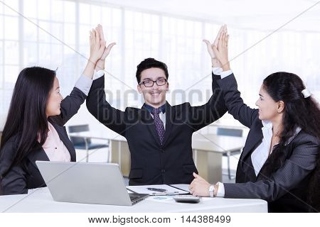 Three multi ethnic business team celebrating their success by raising hands together in the office