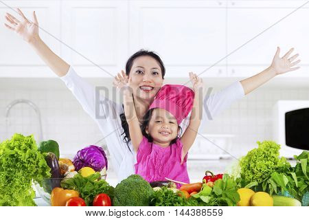 Happy young woman and little girl raise hands together in the kitchen with vegetables on the table