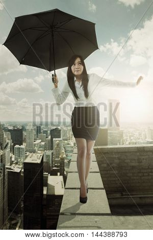 Young businesswoman walking on the rooftop while holding a black umbrella