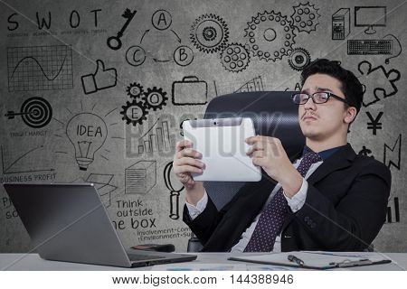Young entrepreneur wearing formal suit and lean on office chair while using tablet and working with laptop on desk