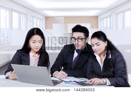 Three multi ethnic employees discussing business plan and strategy with laptop computer in the office