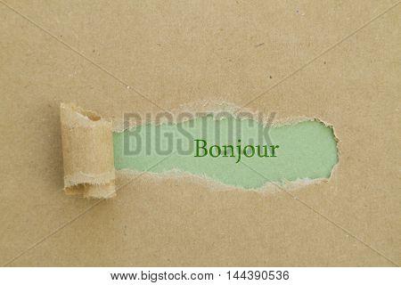 French Bonjour (hello) word written under torn paper.