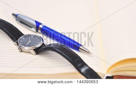 clock and a pen lying on the diary