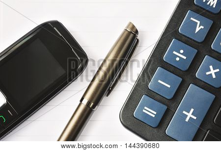 pen, mobile phone and a calculator lying on a notebook