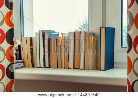 books stand on a windowsill near the window