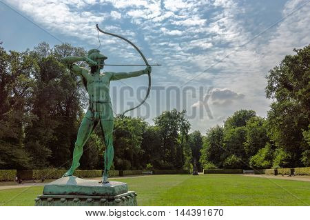 Green bronze archer sculpture in a green grass garden