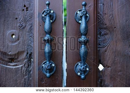 The wooden door and iron handles of an old house