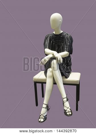 Sitting female mannequin wearing black dress against lilac background. No brand names or copyright objects.
