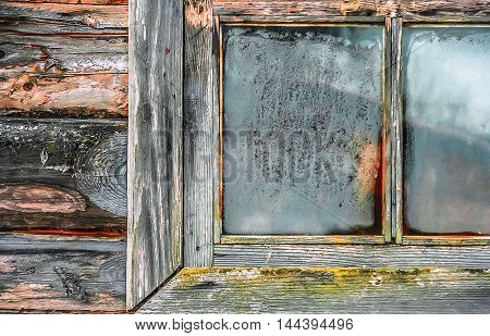 Fragment of the old wooden wall and a frozen window of rustic log hut in the morning sunray closeup.