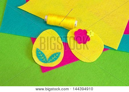 Easter egg ornament set, yellow thread, needle, flower button, colorful felt sheets on a green background. How to sew Easter egg decor. Home decor. Sewing crafts. Step