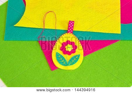 Sewing set for felt Easter egg on a green background. How to sew Easter egg with flower and leaves ornament. Home felt decor. Sewing diy. Step