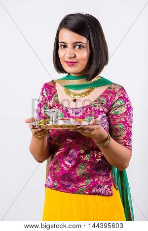 beautiful Indian young girl performing puja, indian girl with pooja thali or puja thali, portrait of a beautiful young lady with pooja thali, isolated overwhite background