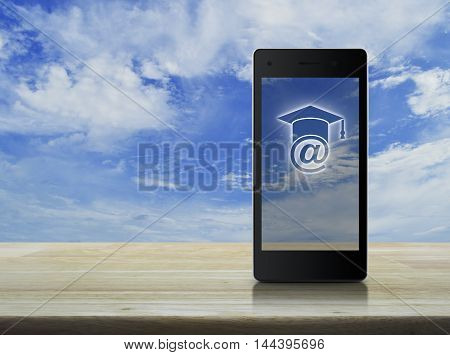 E-learning icon on modern smart phone screen on wooden table over blue sky Study online concept
