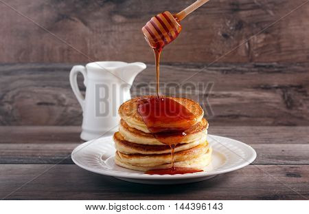 Honey stick pouring honey over stack of pancakes