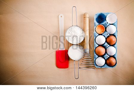 White and brown eggs whisker and cups with flour and sugar top view