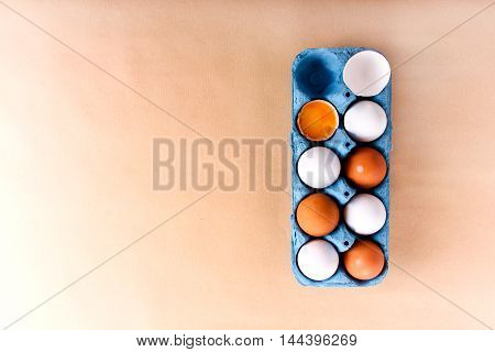 White and brown eggs in cupboard box top view