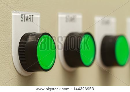 Green start buttons on control panel of machine.