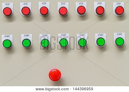 Red emergency and stop switch with green start buttons on control panel of machine. For automatic machine.