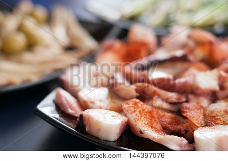 octopus, anchovies, olives, asparagus and coarse salt on plates, traditional snacks, Spain, natural, tasty and healthy dishes