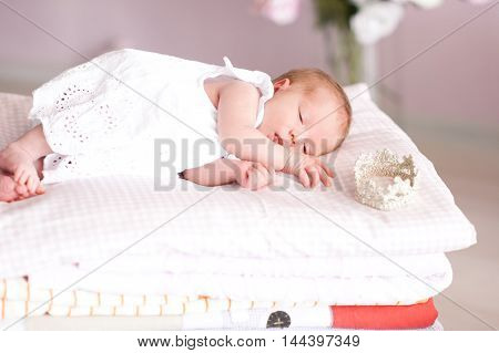 Infant baby girl sleeping wearing white stylish dress in room. Little princess. Childhood.