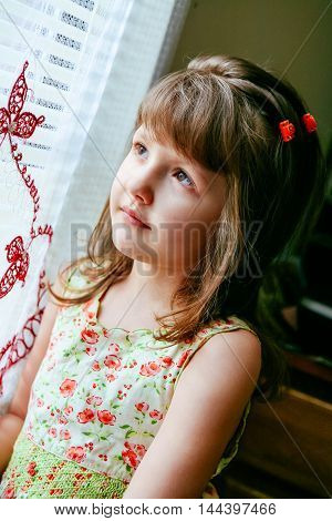 Sad little girl looking at window little girl looking out the window