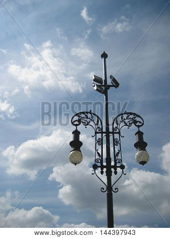 Historic old black and white outside street lantern against blue sky and clouds nature background