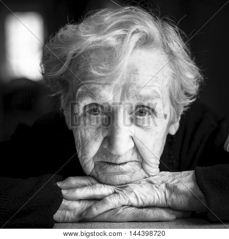 Closeup black and white portrait of an elderly woman.