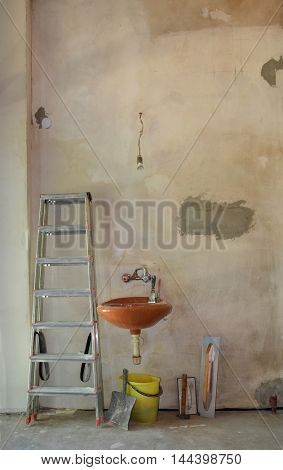 Not renovated wall with ladder and sink. Some tools around.