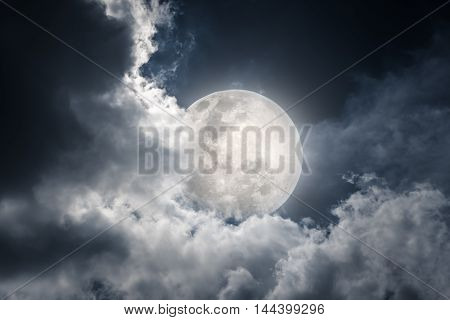 Attractive photo of a nighttime sky with cloudy and bright moon. Beautiful nature use as background. Outdoors.