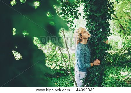 Blonde young man posing in the forest