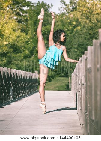 Latin woman dancing ballet in a park with leg raised above her head