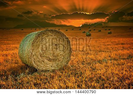 Dramatic sunset in magical countryside with hilly field and rolls of haystack
