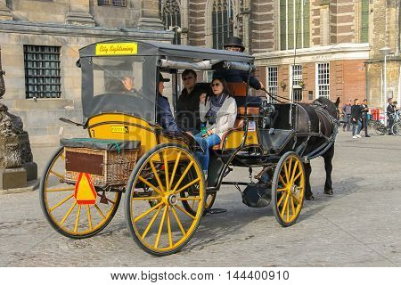 Amsterdam the Netherlands -October 03 2015: Carriage with tourists on Dam Square in historic city centre