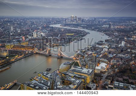 London England - Aerial Skyline view of London with the iconic Tower Bridge Tower of London and skyscrapers of Canary Wharf at dusk