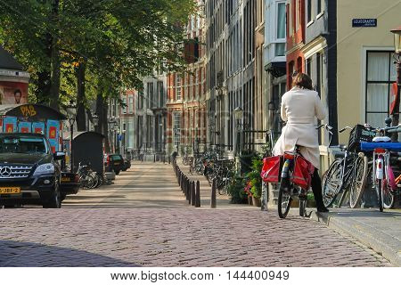 Amsterdam the Netherlands -October 03 2015: Woman riding a bike in historic city centre