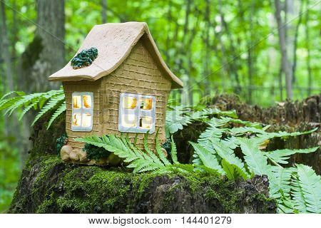 The Concept Of Nature, Green Forest. Clay House On A Wooden Stump With Leaves.