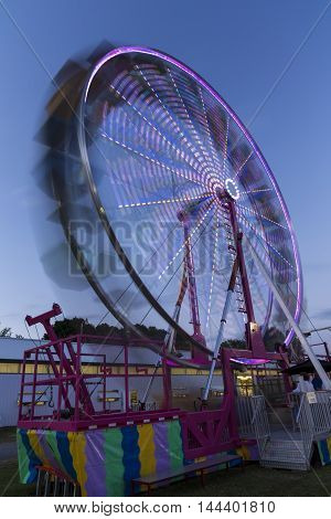 A ferris wheel in motion in the evening.
