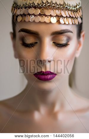 Beautiful girl with perfect skin and wine lips. Picture taken in the studio. Hair accessory and graphic eyebrows.